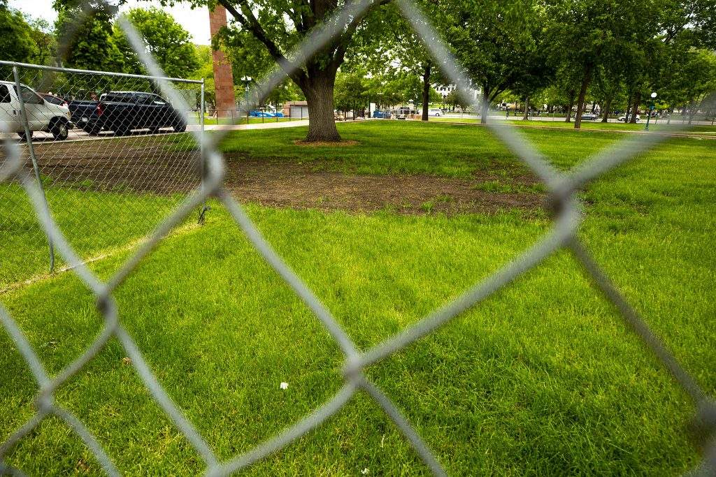 A patch of dirt shows where a large encampment once sat at Veterans Park at Colfax Avenue and Lincoln Street. It's been fenced off since the city swept the camp. May 27, 2021.