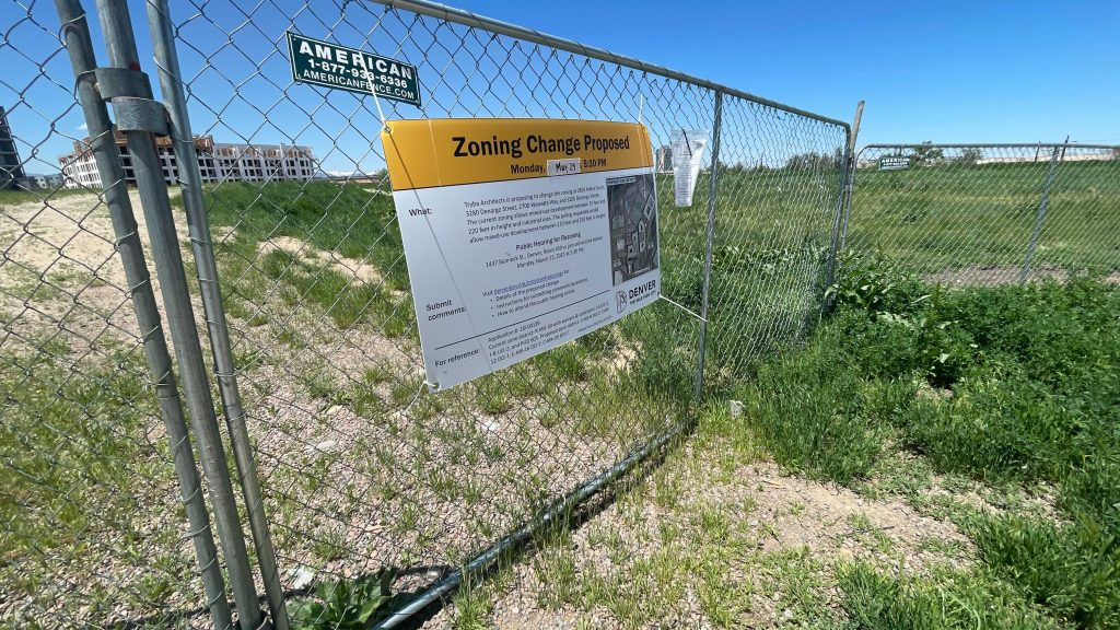 A fence surrounding 2650 Arkins Ct. with a sign on its proposed rezoning on Monday, May 24, in the Five Points neighborhood. (Esteban L. Hernandez/Denverite)