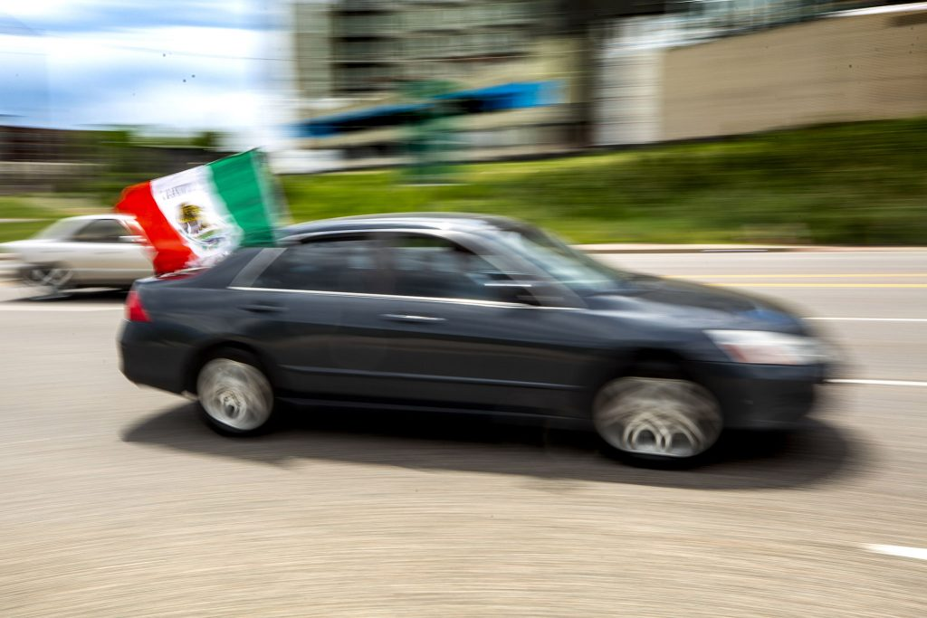 A car flying Mexico's flag heads up Federal Boulevard before the U.S. and Mexico national teams face off in the CONCACAF Nations League finals at Mile High Stadium. June 6, 2021.