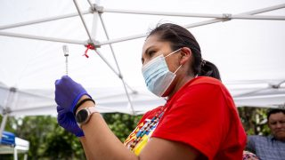Robin Cothley, with Denver Indian Health and Family Services, prepares a Johnson and Johnson COVID-19 vaccine during the talking circle at Governor's Park. June 10, 2021.