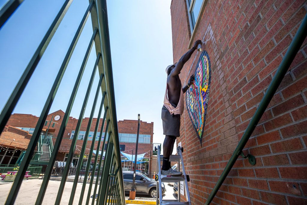 """""""Just"""" Giovannie Dixon paints a frame around a piece in the new Five Points Outdoor Mural Gallery at Five Points Plaza on Welton Street. June 15, 2021."""