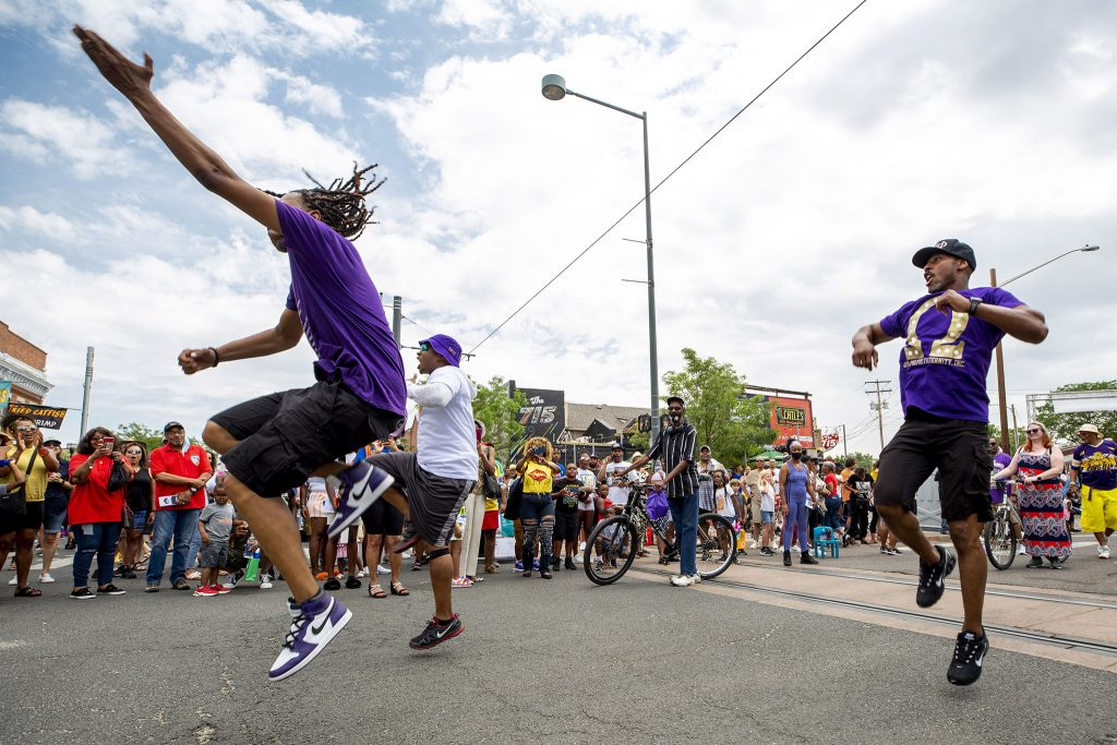 Quincy Shannon, Lindsey Haggerty and Erone Adams dance in the heart of Five Points as they represent Omega Psi Phi in Denver's Juneteenth Parade. June 19, 2021.
