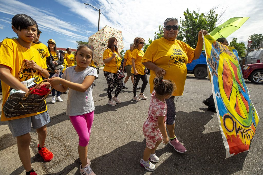GES Coalition member Raymunda Carreon holds her granddaughter's hand during a march to the National Western Center development site. June 26, 2021.