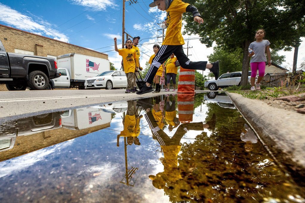 Jack (10) leaps a puddle as members and supporters of the GES Coalition march to the National Western Center development site in protest of public-private partnerships. June 26, 2021.