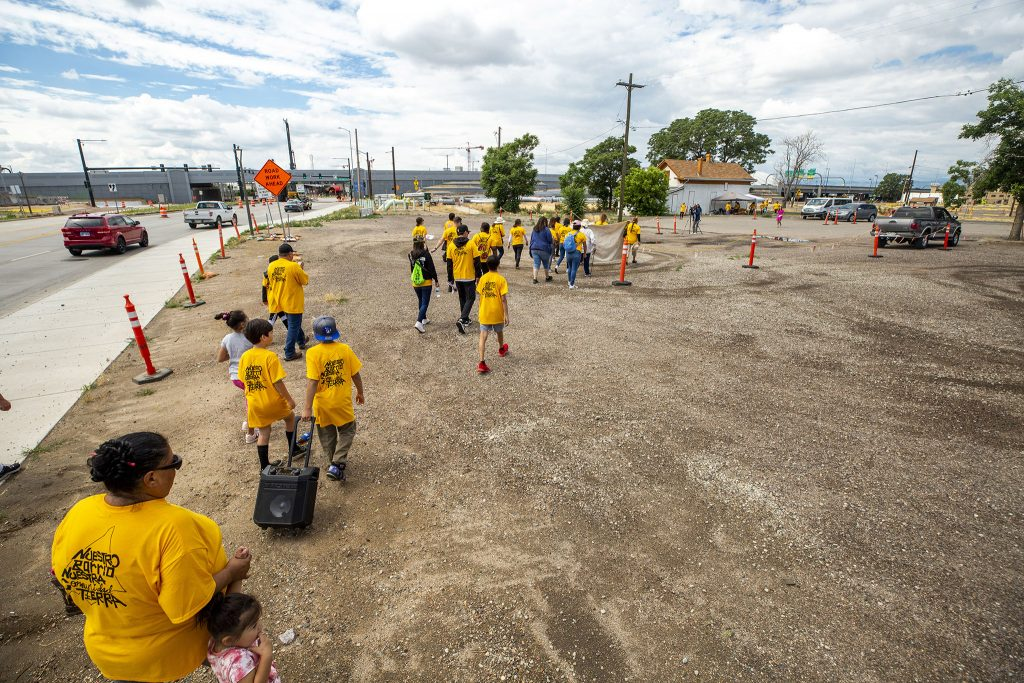 """Members and supporters of the GES Coalition march into the """"Triangle"""" parcel of the National Western Center development site, during a protest against public-private partnerships. June 26, 2021."""