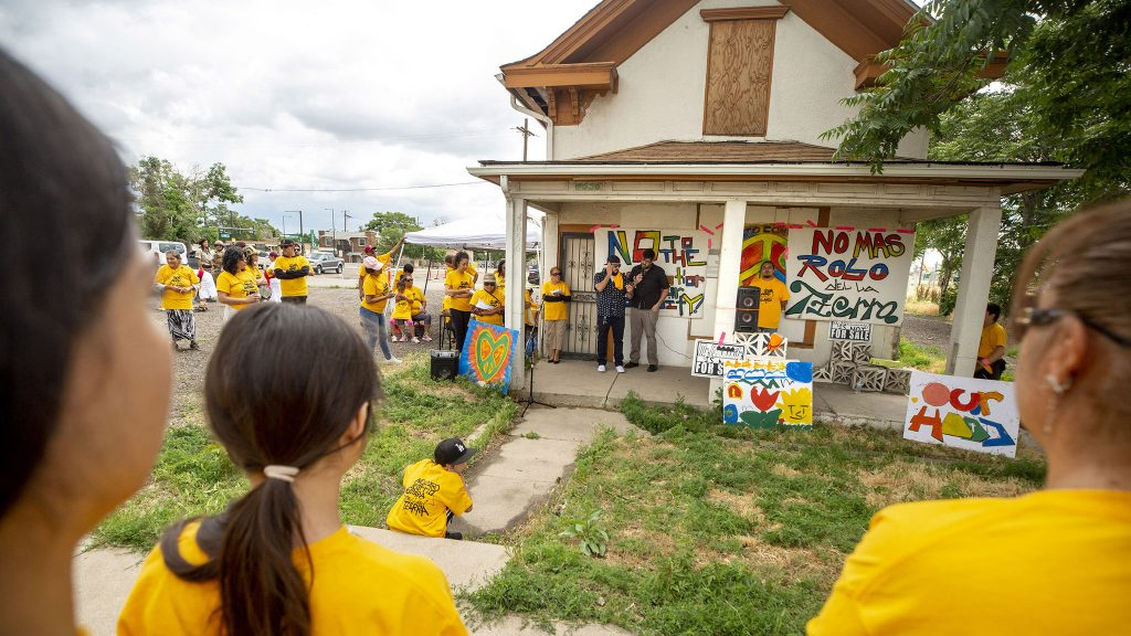 """David Torres speaks from the porch of his old family home during a protest against public-private partnerships on the """"Triangle"""" parcel of the National Western Center development site. June 26, 2021."""