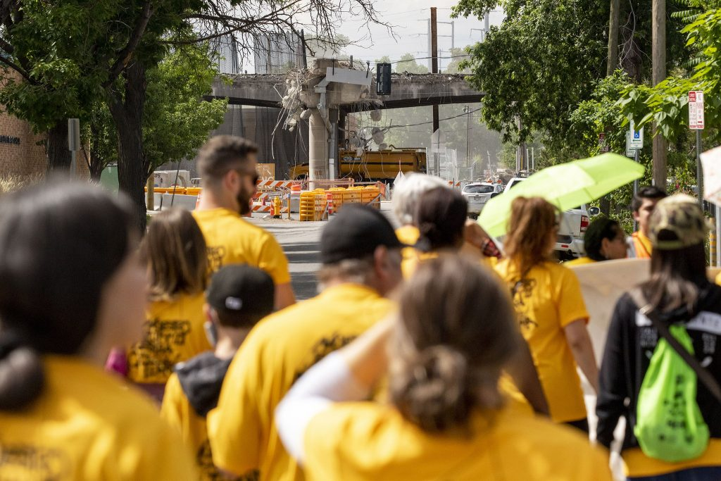 The I-70 viaduct, in mid-demolition, is seen in the distance as members and supporters of the GES Coalition march to the National Western Center development site. June 26, 2021.