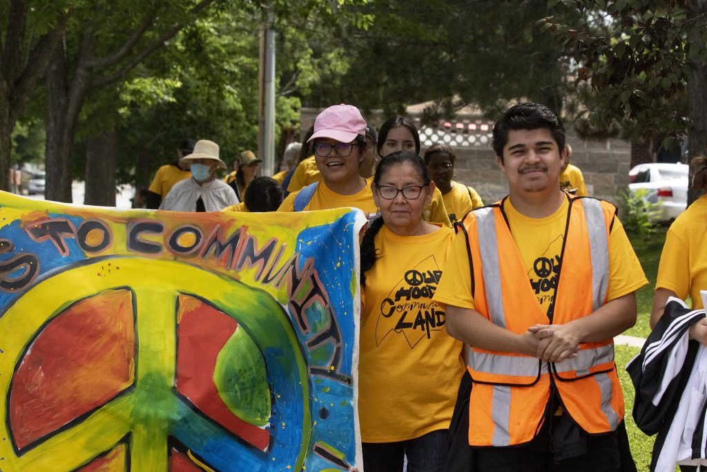 GES Coalition member Ruben Sanchez (right) marches to the National Western Center development site in protest of public-private partnerships. June 26, 2021.