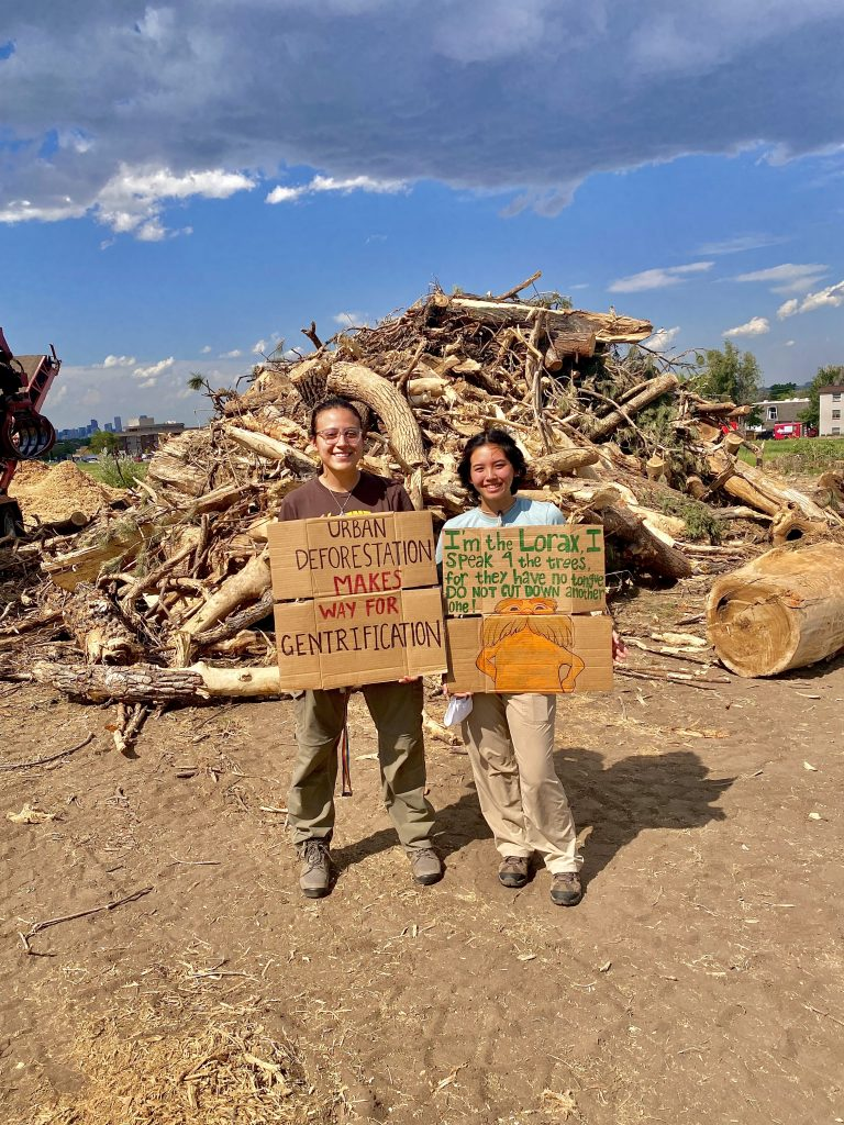 Damar Garcia (left) and Kealohilani Minami hold up signs in front of a pile of cut down trees at the Loretto Heights campus. June 13, 2021
