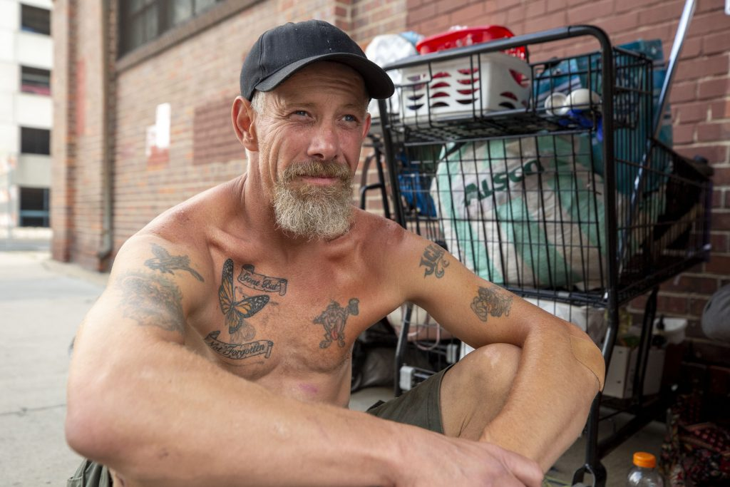 John Listenberger sits on a Welton Street sidewalk after he was forced to move his belongings away from a city encempent sweep site around the corner. July 1, 2021.