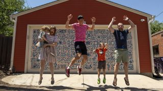 Charlo G. Walterbach poses with Betsy Atkinson and Nick Evans and their kids, Theo and Darby, in front of Walterbach's mural on the family's garage near Cheesman Park. July 5, 2021.