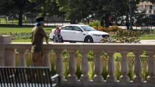 A Denver Police officer sits in a cruiser parked conspicuously in the middle of Civic Center Park. July 10, 2021.