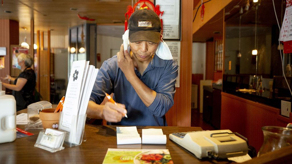Jiarong Wang, owner of JJ Bistro, takes a call-in order around lunchtime. July 12, 2021.