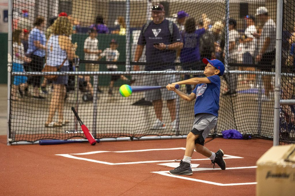 """A kid smacks a ball at the """"Play Ball"""" exhibition at the Colorado Convention Center. July 13, 2021."""