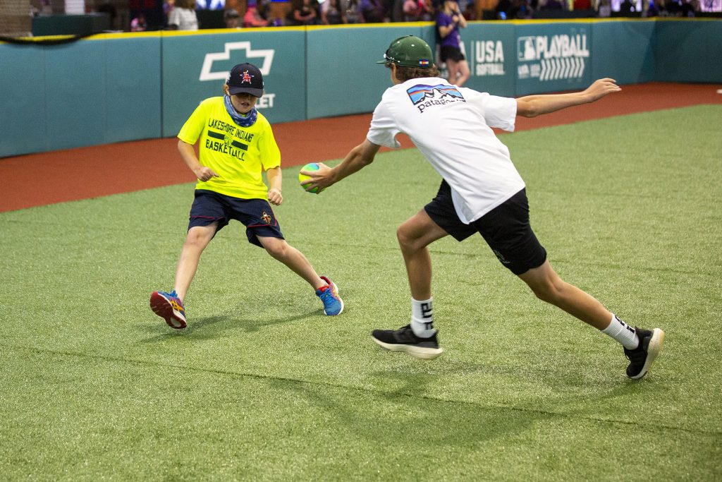 """A kid dodges an out at the """"Play Ball"""" exhibition at the Colorado Convention Center. July 13, 2021."""