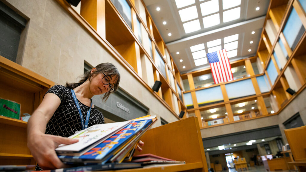 Children's Librarian Amy Seto Forrester stocks some of the stacks that will be available on main floor of the Denver Public Library's Central Library on Friday, July 17, 2021. The facility will reopen with limited access to the first floor, computer rooms, and social service facilities to the public on Sunday, July 16 after being closed first by the COVID-19 pandemic, and then owing to extensive renovations.