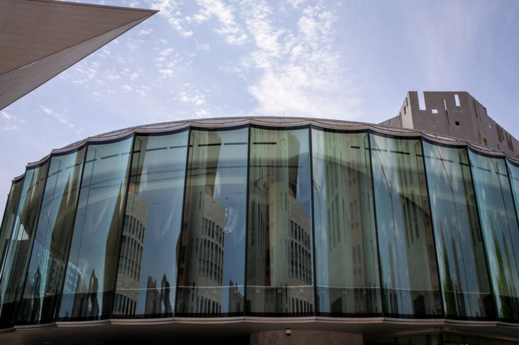 The Denver Public Library's Central Library is reflected in the windows of the new Sie Welcome Center of the Denver Art Museum on Friday, July 16, 2021. The Central Library will reopen with limited access to the first floor, computer rooms, and social service facilities to the public on Sunday, July 16 after being closed first by the COVID-19 pandemic, and then owing to extensive renovations.
