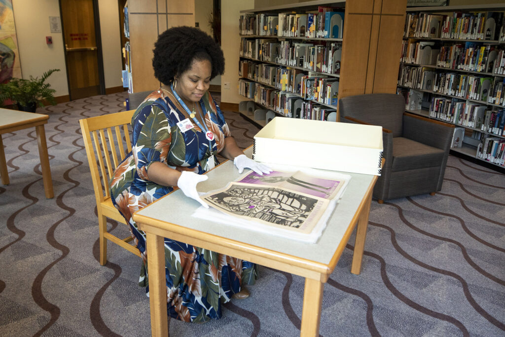 Senior librarian Jameka Lewis handles an issue of The Black Panther on the second floor of the Blair-Caldwell African American Research Library on Welton Street. July 22, 2021.