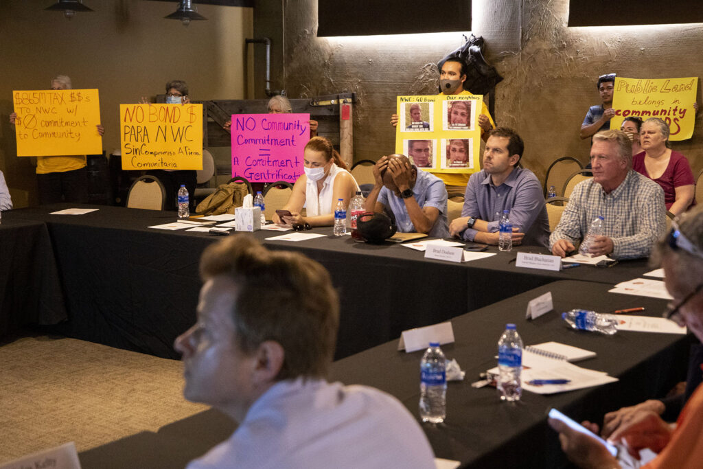 Activists with the GES Coalition stand with protest signs during a meeting of the National Western Center Citizens Advisory Committee in a NWC conference room in Elyria Swansea. July 7, 2021.