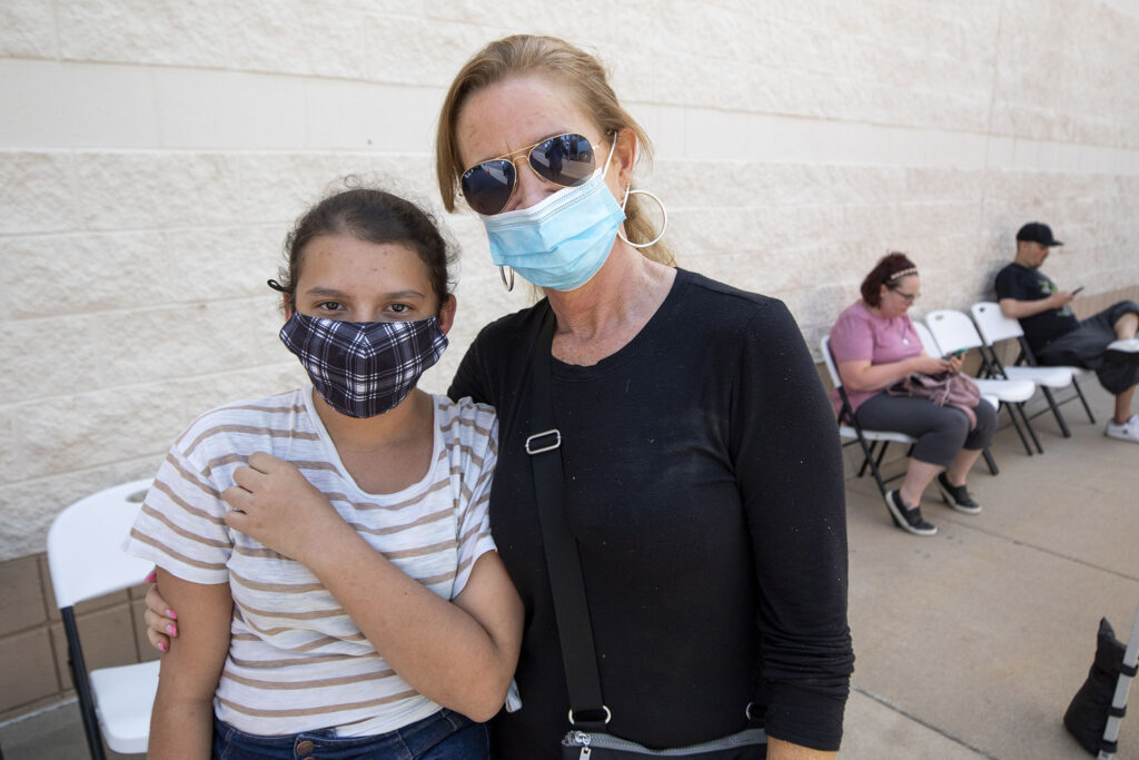 Cynthia Martir stands with her grandmother,Sharon Carter, after she got a COVID-19 shot at a mobile clinic at Chambers Road and Colfax Avenue in Aurora. July 23, 2021.