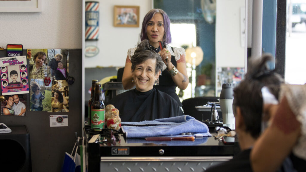 Cue Perez, owner of Babooshka hair salon on East Colfax Avenue, works on Diane D'Angelo's hair on a Saturday morning. July 24, 2021.
