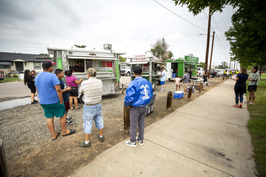 Elyria Swansea residents wait in line for free tacos, a concession from Xcel Energy because gas lines here have been out since Wednesday. July 31, 2021.