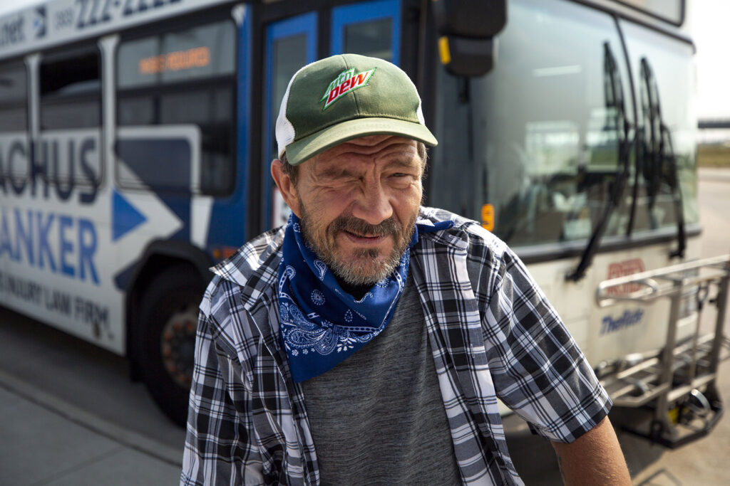 Bill Friend prepares to board a bus at RTD's Peoria Street station in Aurora. Aug. 10, 2021.