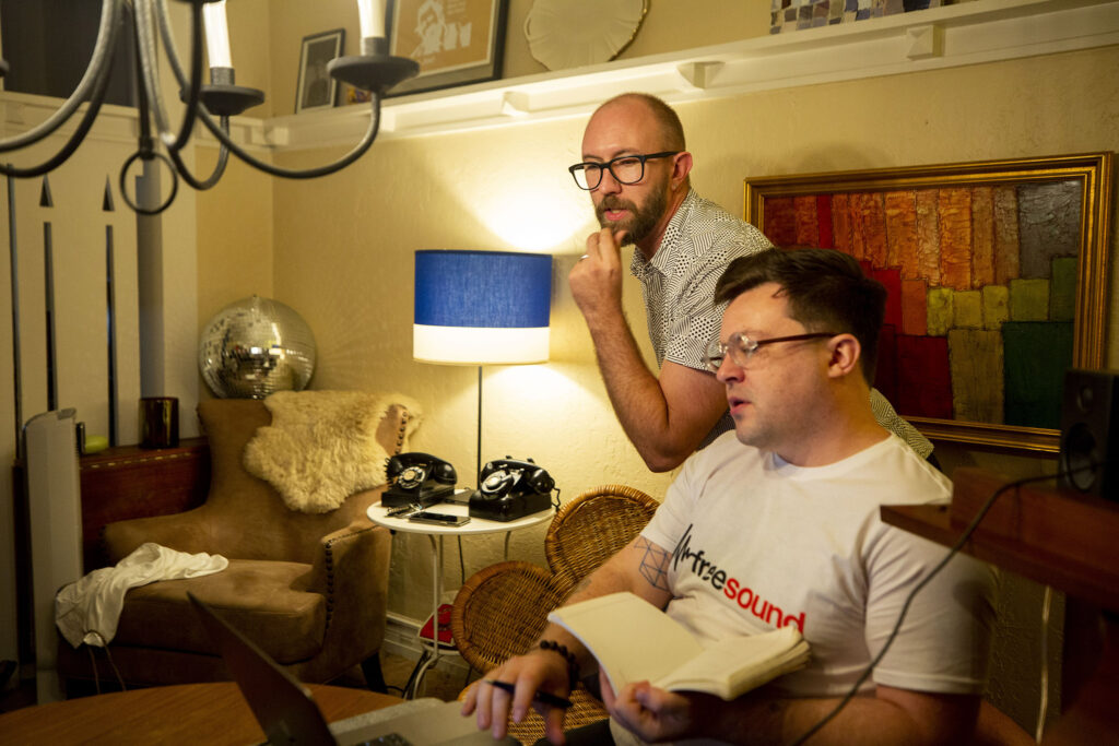 """Nathan Hall and Isaac Linder work out the score of """"UNBOUND: A New Opera"""" in Hall's living room. Aug. 12, 2021."""