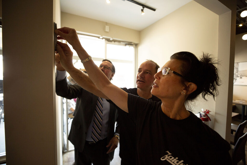 Beth Ginsberg (right to left) and Joel Appel stick a mezuzah onto the entrance of the new Zaidy's Deli and Bakery location off Leetsdale Drive in Washington Virginia Vale. Aug. 17, 2021.