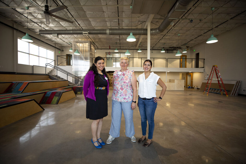 Senior librarian Mónica Lozano, neighborhood services manager Jenny LaPerriere and DPL communications manager Oliva Gallegos stand inside the future Denver Public Library branch at the ArtPark Community Hub off Brighton Boulevard. Aug. 19, 2021.