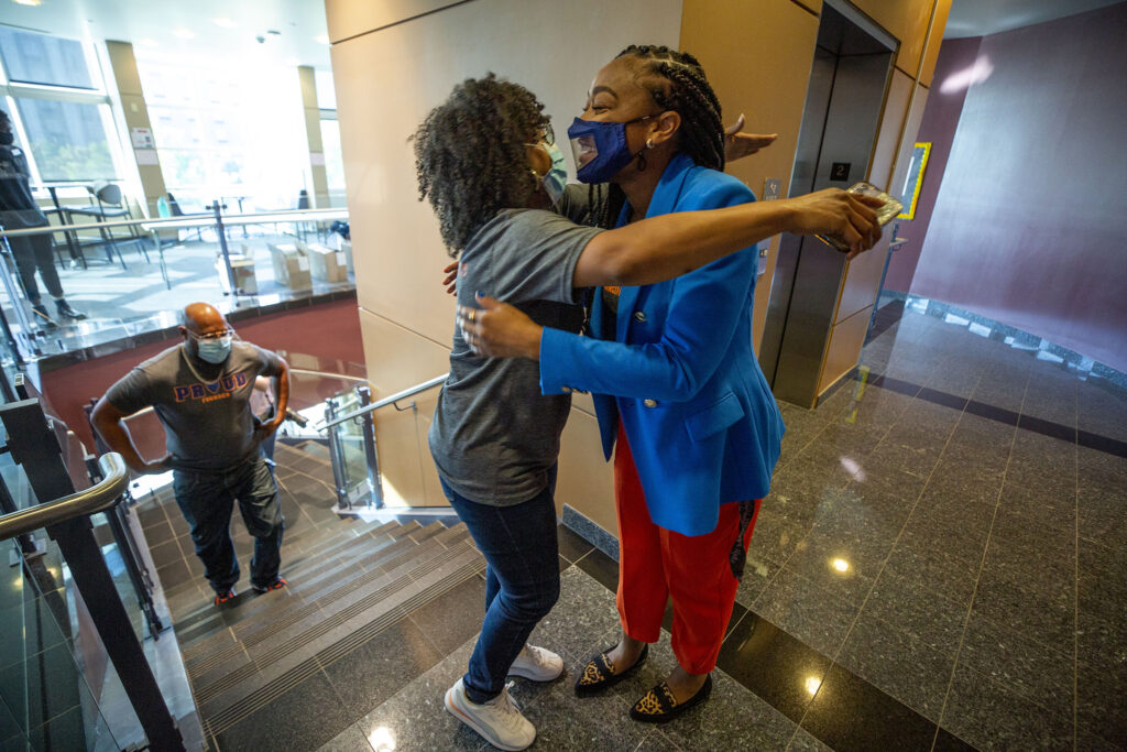 Principal Shakira Abney-Wisdom (right) embraces Robert F. Smith STEAM Academy co-founder Samantha Pryor on the school's inaugural first day. Aug. 23, 2021.