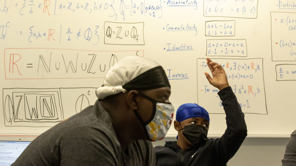 Steve Griffin raises his hand in Najja Shakir Al-Islam's classroom on the inaugural first day of school at Robert F. Smith STEAM Academy. Aug. 23, 2021.