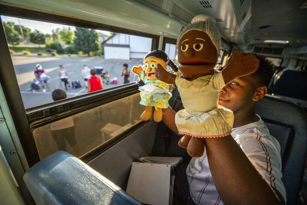 """Darrius Stewart holds Norma Jean (right) and Lynn, who are puppers, during a rehearsal of the play """"Sojourners Project: Busing"""" in the parking lot of the Rising Star Missionary Baptist Church in Aurora. Aug. 23, 2021."""