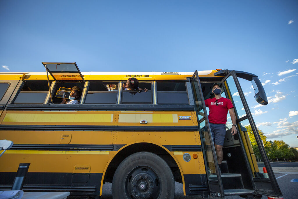 """Darrius Stewart (left to right), Faith Angelise Goins-Simmons and Patrick Mueller hang out of a school bus during a rehearsal of the play """"Sojourners Project: Busing"""" in Aurora. Aug. 23, 2021."""