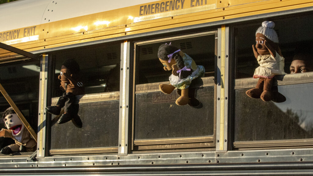"""Puppets hang out of a school bus during a rehearsal of the mobile play """"Sojourners Project: Busing"""" in the parking lot of the Rising Star Missionary Baptist Church in Aurora. Aug. 23, 2021."""