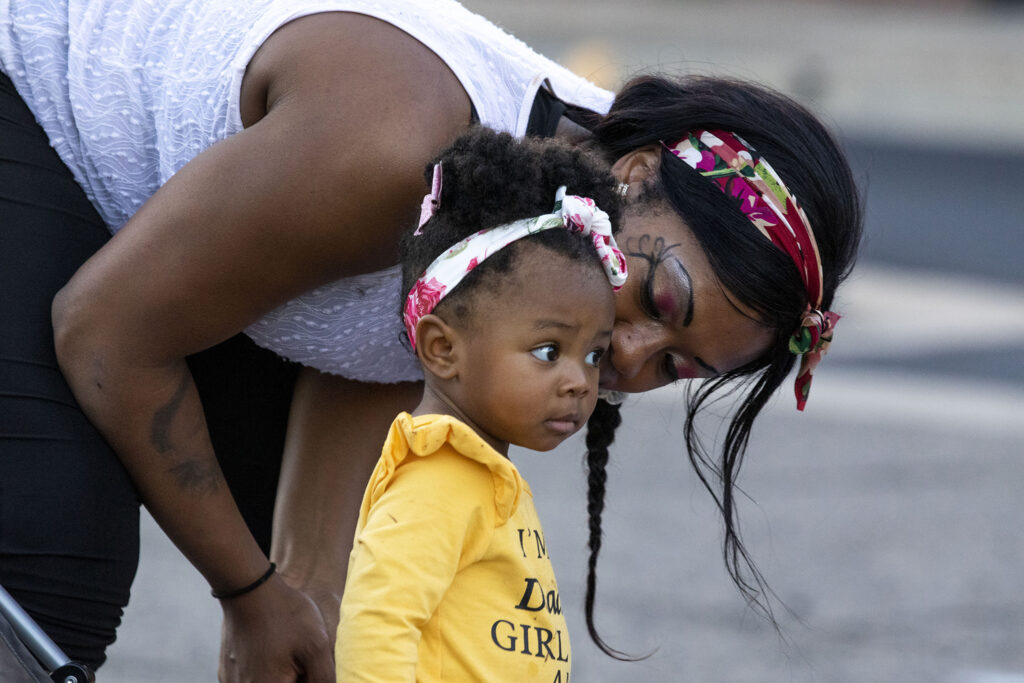 """Faith Angelise Goins-Simmons kisses her daugter, Lala, during a rehearsal of the mobile play """"Sojourners Project: Busing"""" in the parking lot of the Rising Star Missionary Baptist Church in Aurora. Aug. 23, 2021."""