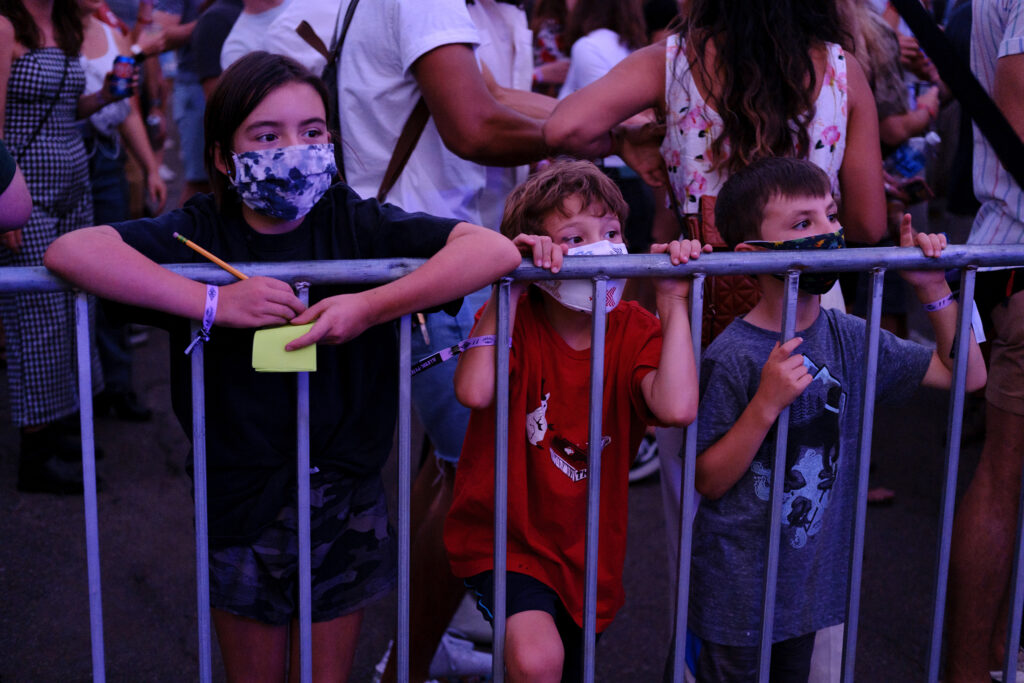 From left, Gloria, 10, Pablo, 7, and August, 6, watch a performance at the Underground Music Showcase main stage in Denver on Friday, August 27, 2021. They were among the only people masked at the event, since it was mostly adults and proof of vaccination or a negative COVID-19 test was required.