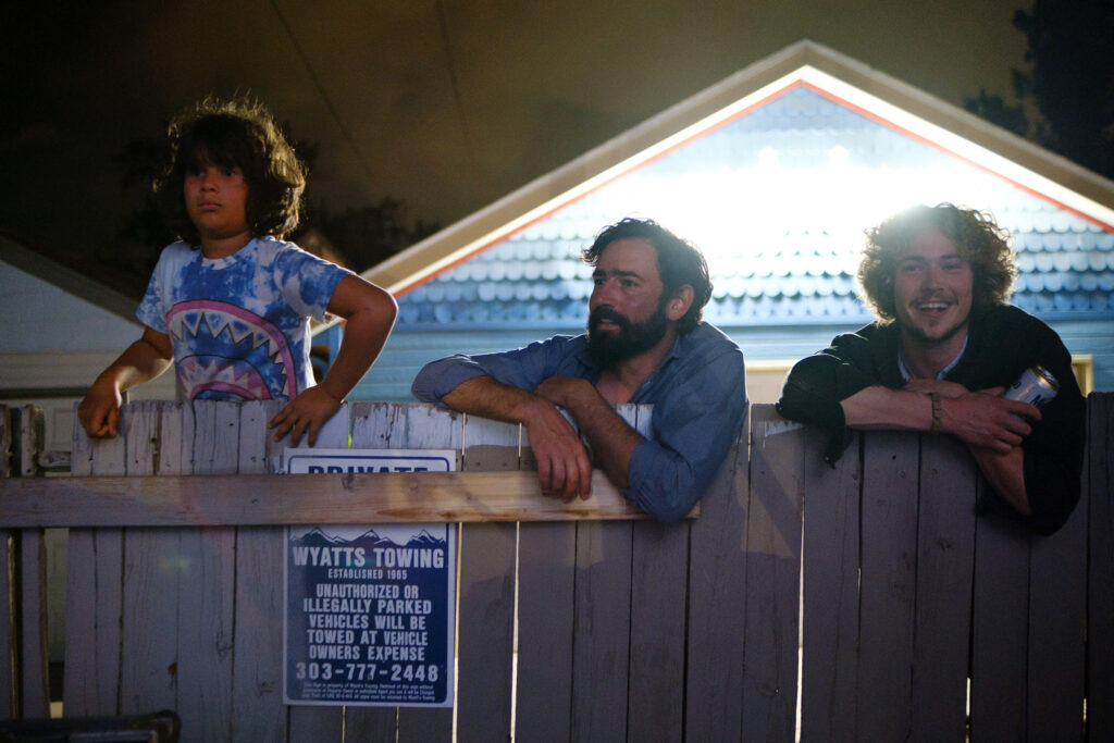 Silver Jessemann, 8, his father, Matthew Jesseman, and friend Johnny Naffah watch a performance at the Underground Music Showcase main stage over the fence from their neighborhood alleyway in Denver on Friday, August 27, 2021.