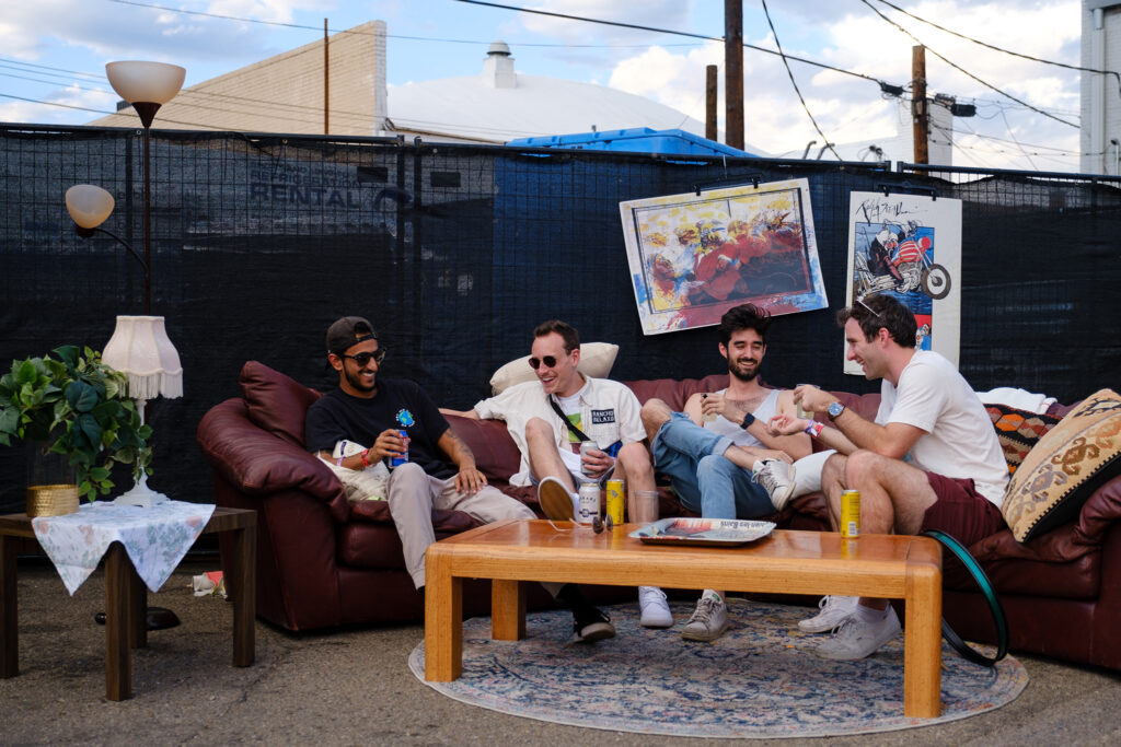 From left, friends Dan Haque, Schmike Vienneau, John welch and Brendan Murphy hang out at the Goodwill pop-up while waiting to see Pinegrove at the Underground Music Showcase main stage in Denver on Friday, August 27, 2021.