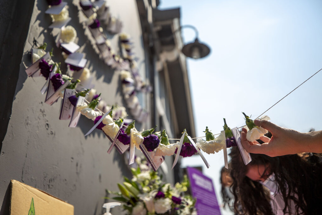 Kat Humphries strings names and flowers on a garland at the Harm Reduction Action Center in honor of Overdose Awareness Day. Aug. 31, 2021.