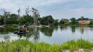 A raft full of divers from the Denver Fire Department scans Duck Lake at City Park on Aug. 3, 2021. Authorities say they were searching for a person who witnesses  said rode a bike into the water and did not resurface.