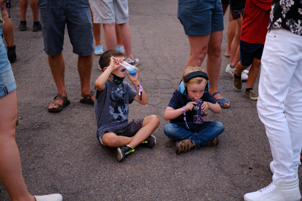 Six-year-old August, left, and Jude, 5, enjoy drinks as their parents socialize in between bands at the Underground Music Showcase main stage in Denver on Friday, August 27, 2021.