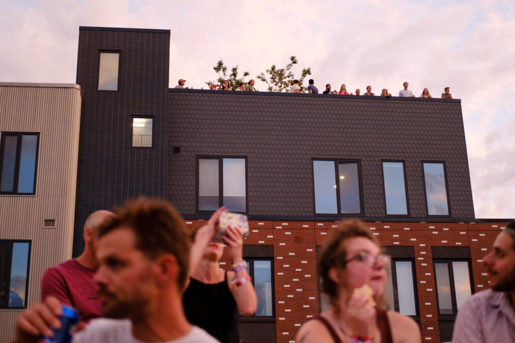 People watch a performance at the Underground Music Showcase main stage from their apartment rooftop in Denver on Friday, August 27, 2021.