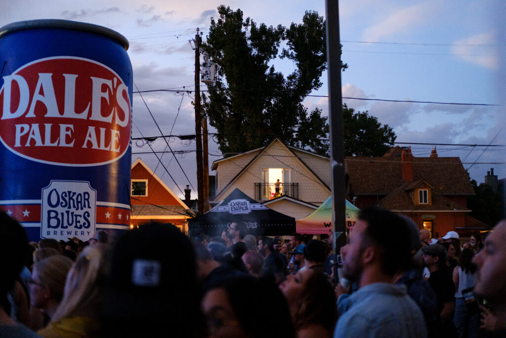 People watch a performance at the Underground Music Showcase main stage from their home in Denver on Friday, August 27, 2021.