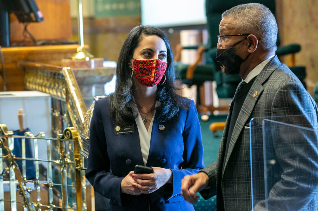 Colorado's first Muslim lawmaker, freshman Rep. Iman Jodeh of Arapahoe County, speaks with Rep. Tony Exum of Colorado Springs on the House floor as the Colorado General Assembly opened its 2021 session on Wednesday, Jan. 13. Both are Democrats.