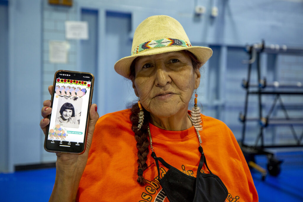 Ruby Sanchez holds a photo of herself as a kid, taken around the time she was taken to the St. Francis Indian School in South Dakota. Sept. 14, 2021.