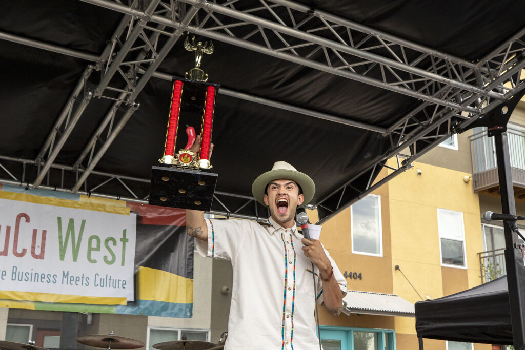 Diego Florez hollers as he holds up the top trophy for the Westwood Chile Fest's chile eating contest . Sept. 11, 2021.