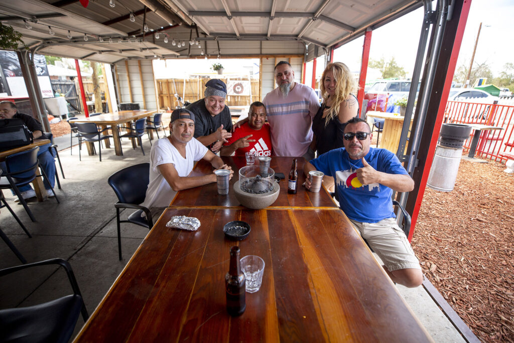 """Boogie Down owner Ron Martinez (right to left), Jennifer and Ernie Lopez, Ed Martinez, """"Juice J Rod"""" and Rich Medina hang out on Boogie Down's Morrison Road patio. Sept. 13, 2021."""