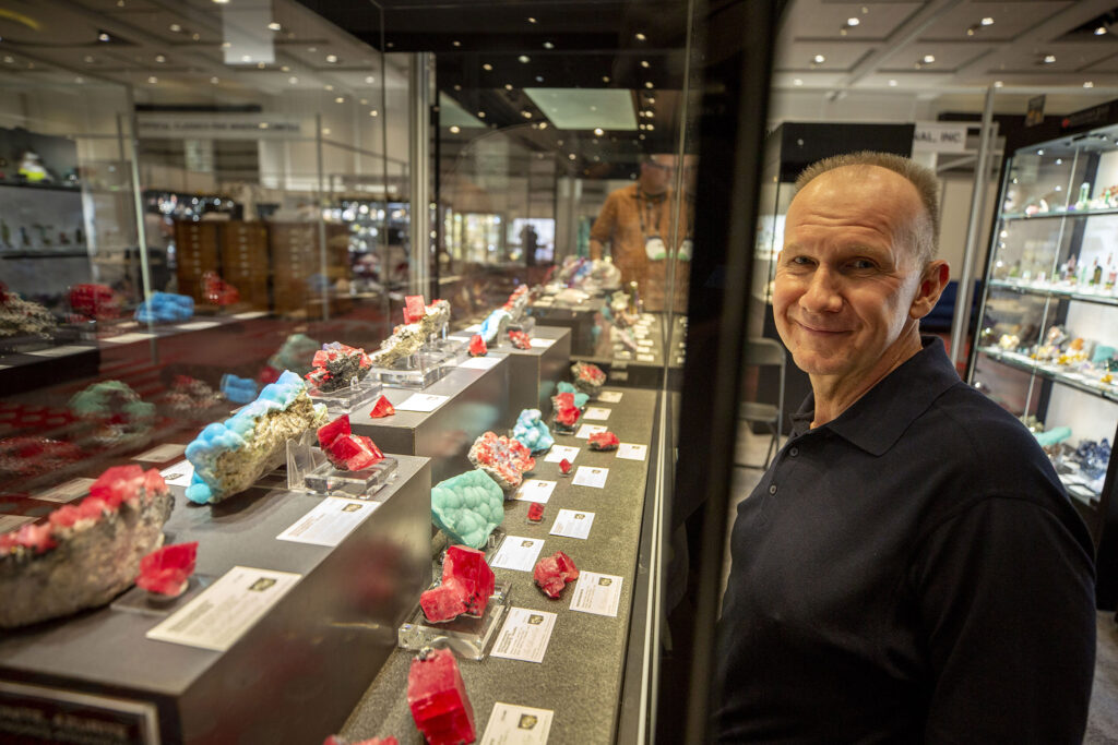 Gem dealer Bryan Lees stands with his display at the the Hardrock Summit inside the Colorado Convention Center, Sept. 15, 2021.