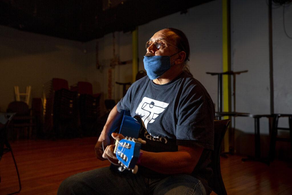 """Director Anthony Garcia strums a tune as his cast rehearses """"El Corrido del Barrio"""" at Su Teatro. Sept. 15, 2021."""